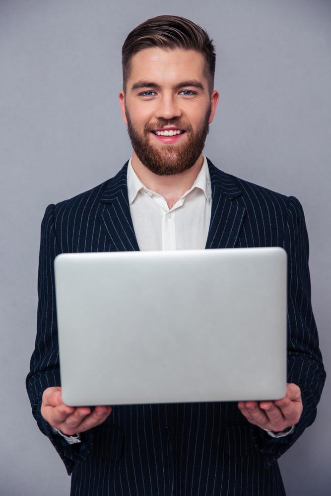 Portrait of a happy businessman holding laptop