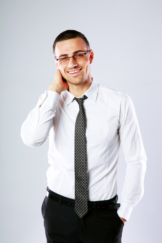 Portrait of a happy businessman on gray background