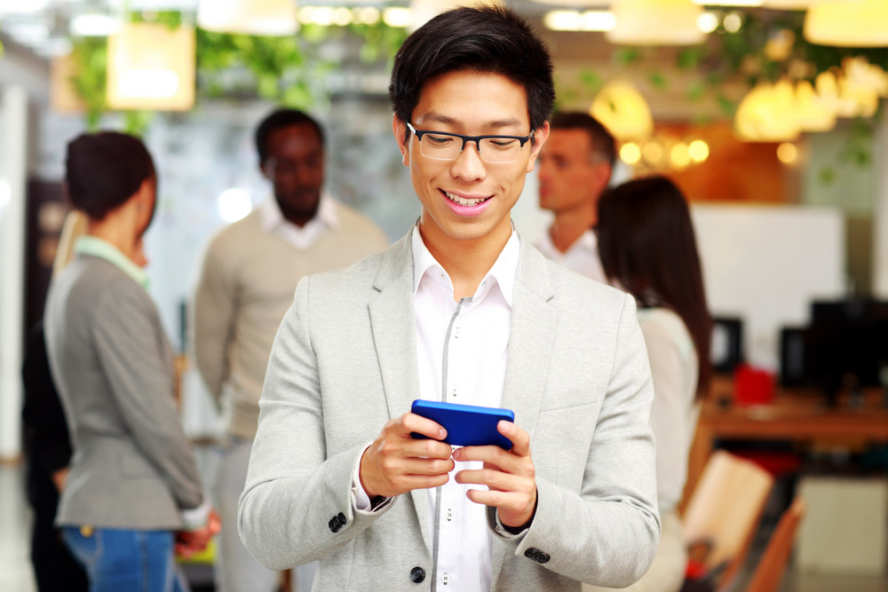 Portrait of a happy businessman using smartphone in front of colleagues