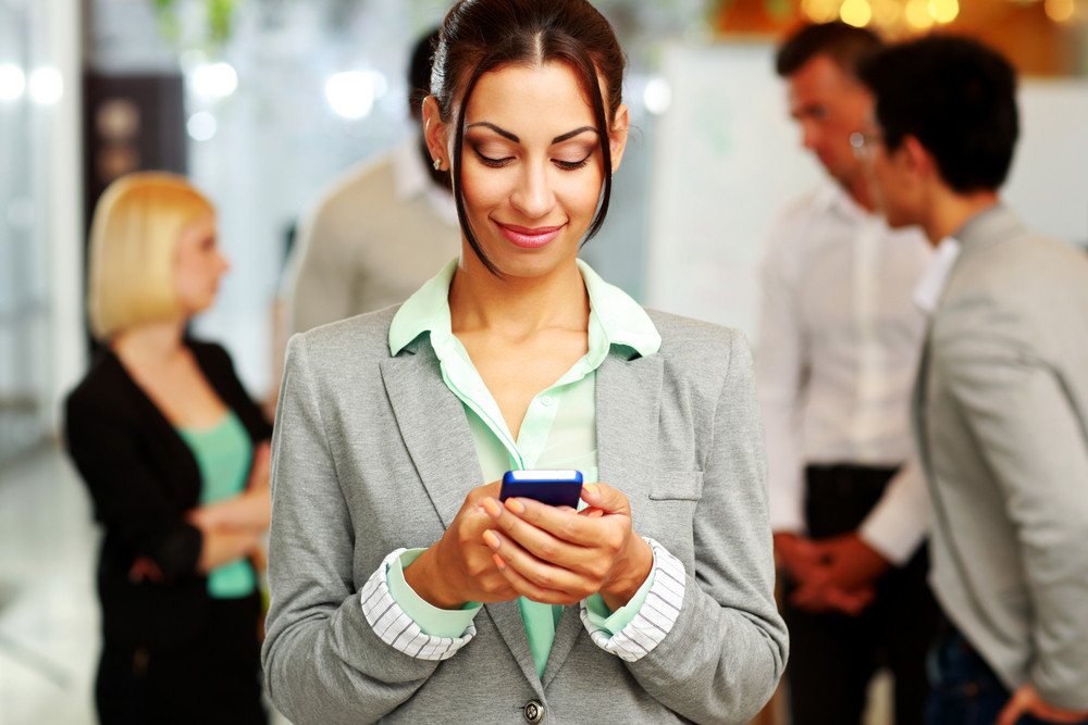 Portrait of a happy businesswoman using smartphone in front of colleagues
