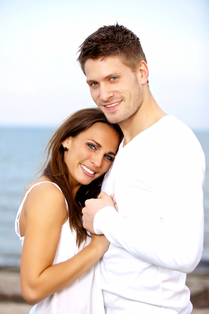 Portrait of a happy couple holding each other's hands posing with the sea as a background