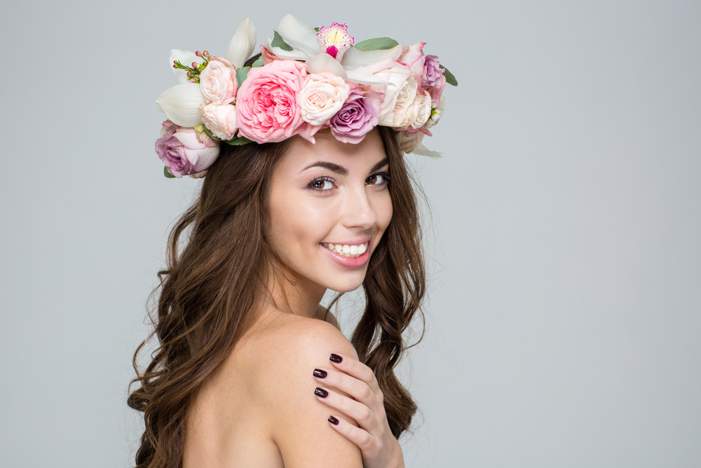 Portrait of a happy cute woman with wreath from flowers on head posing over gray background