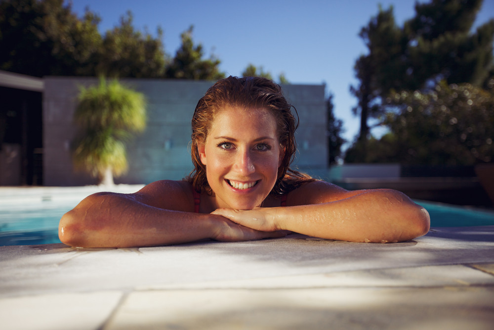Portrait of a happy young woman at edge of a swimming pool looking at camera. Caucasian female model enjoying in the pool on a hot summer day.