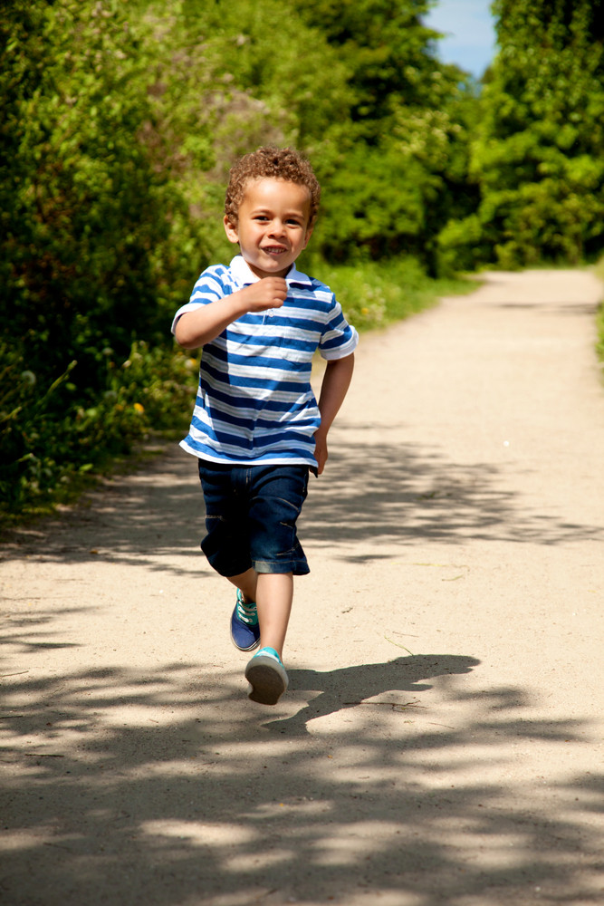 Portrait of a little boy running and having fun on a sunny day
