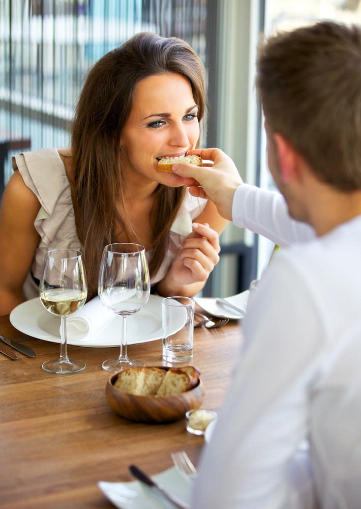 Portrait of a man feeding bread to his girlfriend