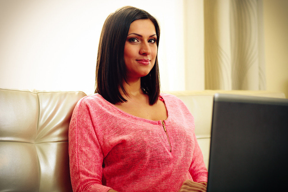 Portrait of a mature happy woman sitting with laptop at home