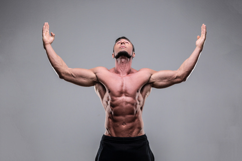Portrait of a muscular man with raised hands up over gray background ...