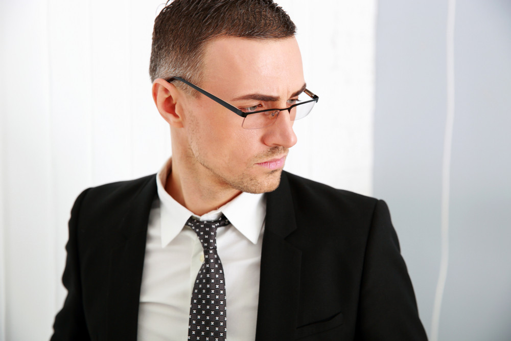 Portrait of a pensive businessman in glasses at office