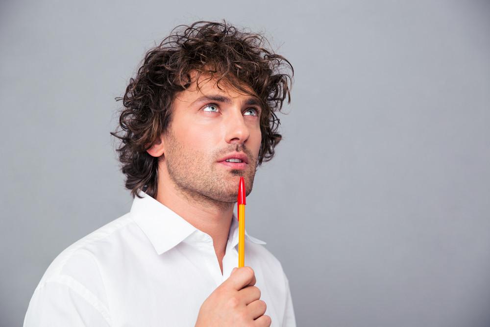 Portrait of a pensive businessman with pen