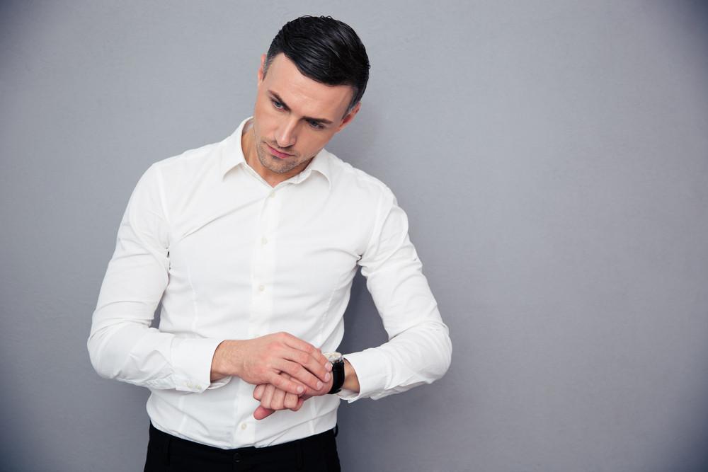 Portrait of a pensive businessman with wristwatch