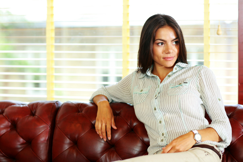 Portrait of a pensive businesswoman sitting at the sofa in office