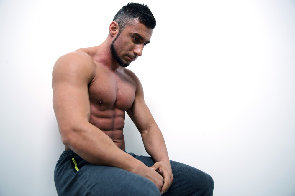 Portrait of a pensive muscular man over gray background