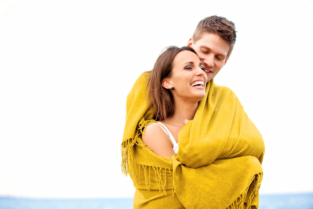 Portrait of a romantic couple embracing while wrapped with a blanket
