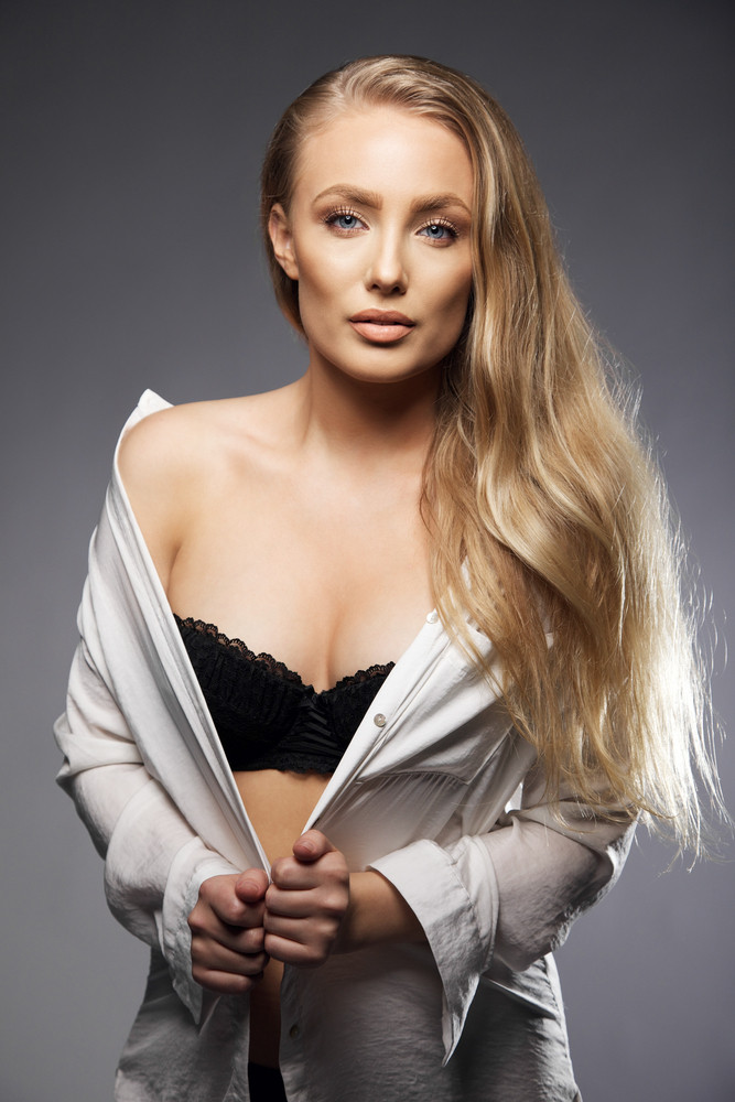 Portrait of a sexy young woman wearing black lingerie and shirt on grey background. Caucasian female fashion model.