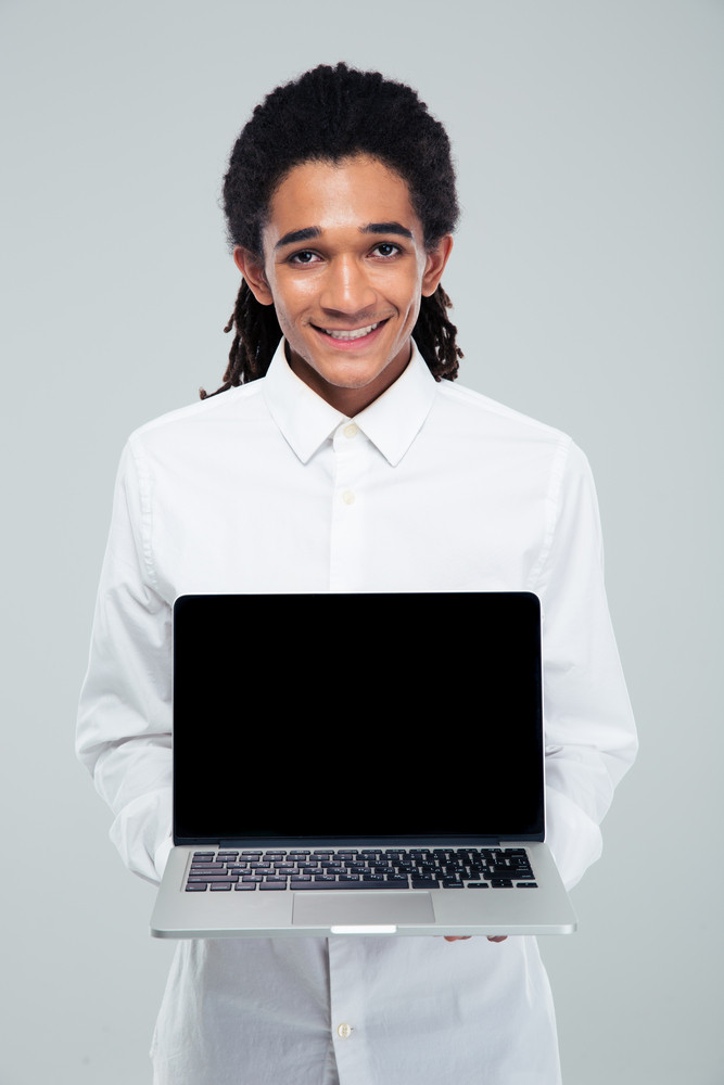 Portrait of a smiling afro american businessman showing blank laptop screen over gray background