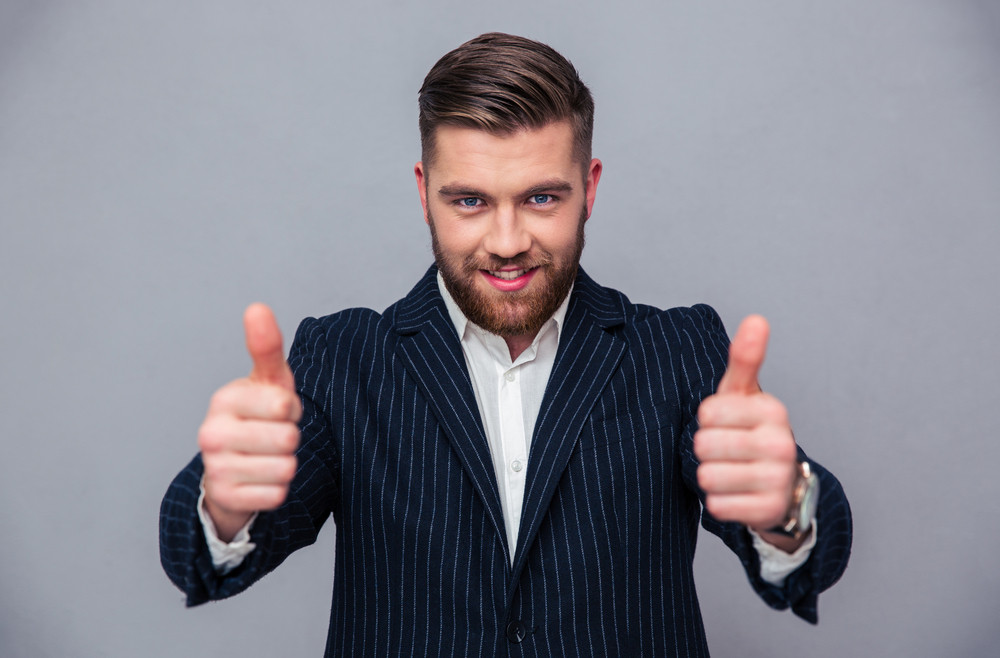 Portrait of a smiling businessman showing thumbs up