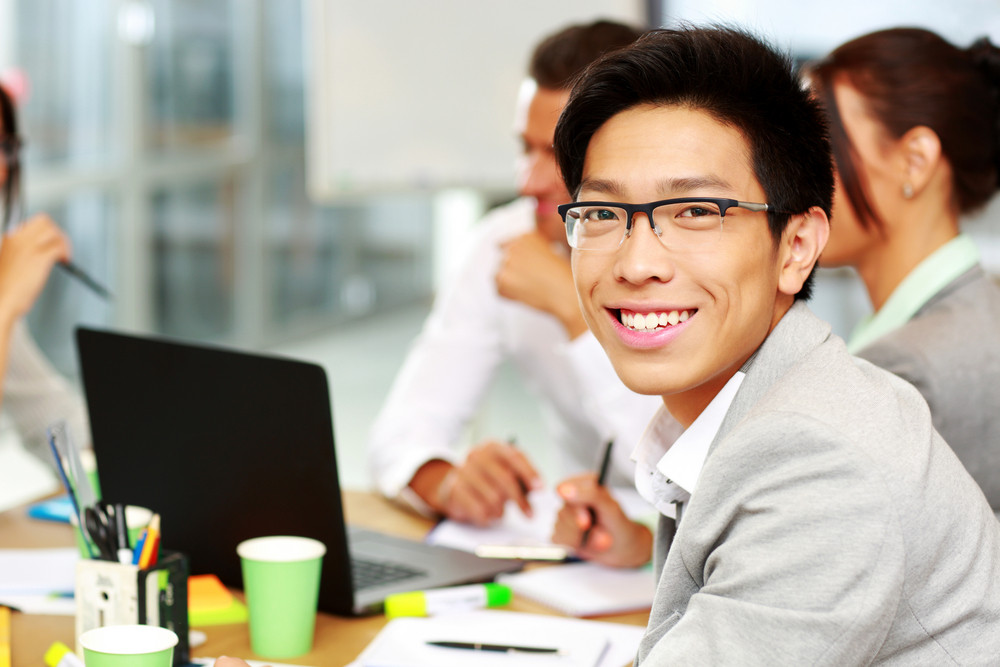 Portrait of a smiling businessman sitting in front of colleagues