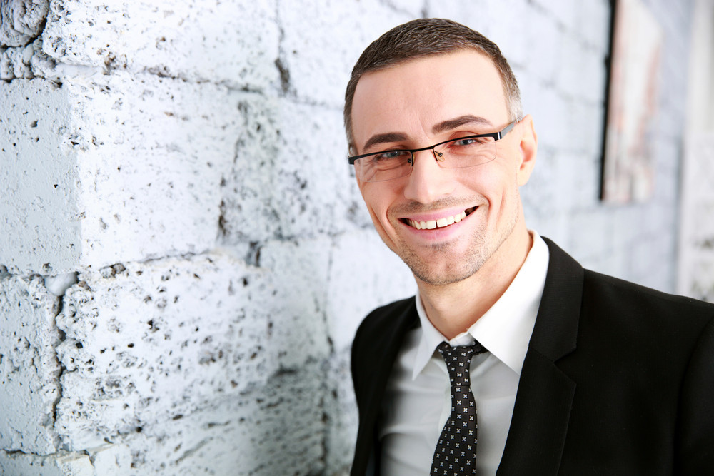 Portrait of a smiling businessman standing near brick wall