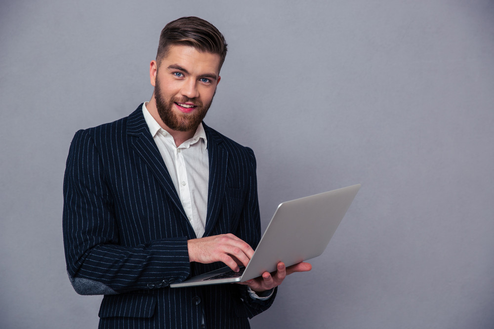 Portrait of a smiling businessman using lapto