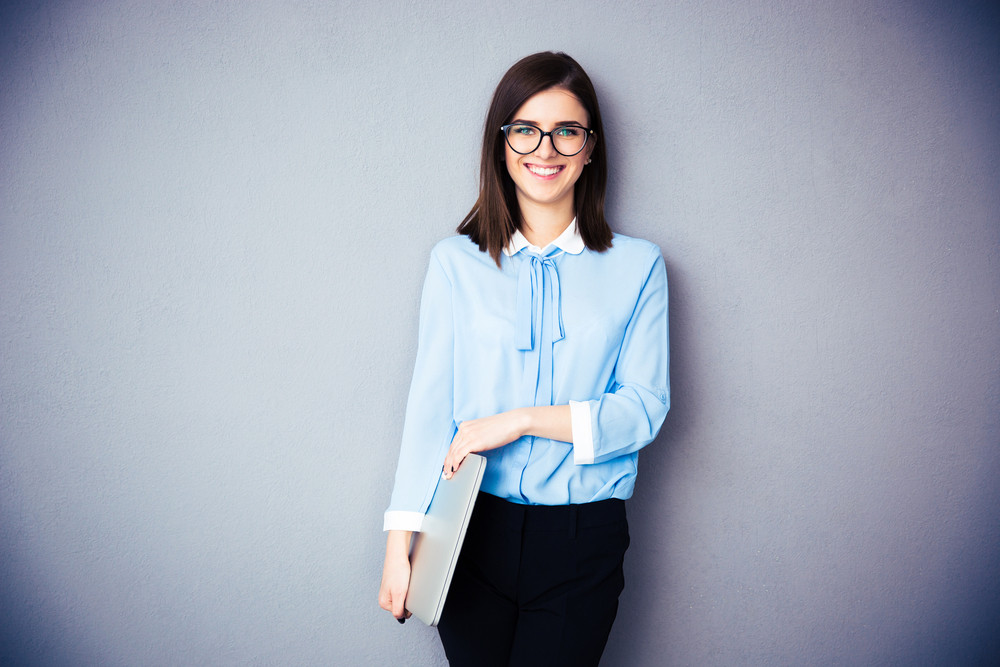 Portrait of a smiling businesswoman holding laptop over gray background. Wearing in blue shirt and glasses. Looking at camera