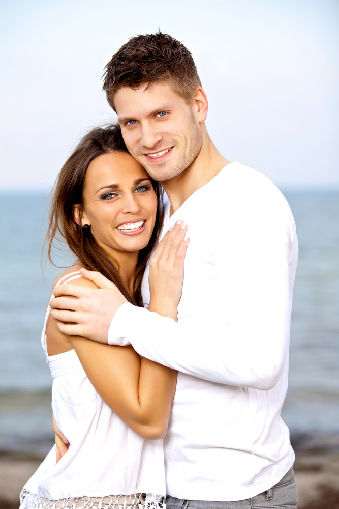 Portrait of a smiling couple posing with the beach as background