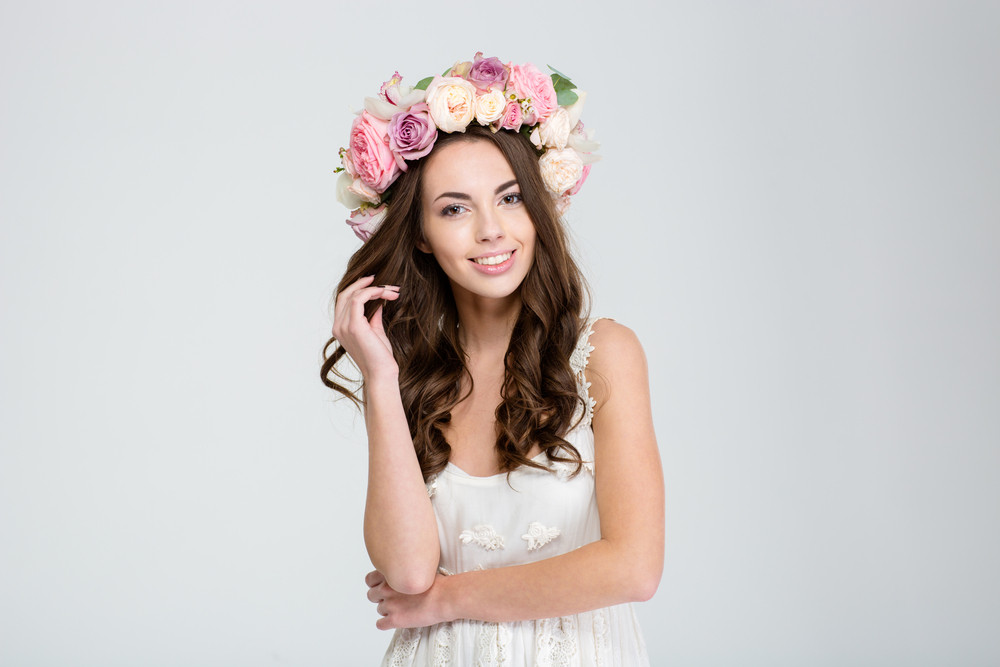 Portrait of a smiling cute woman with wreath of roses looking at camera isolated on a white background