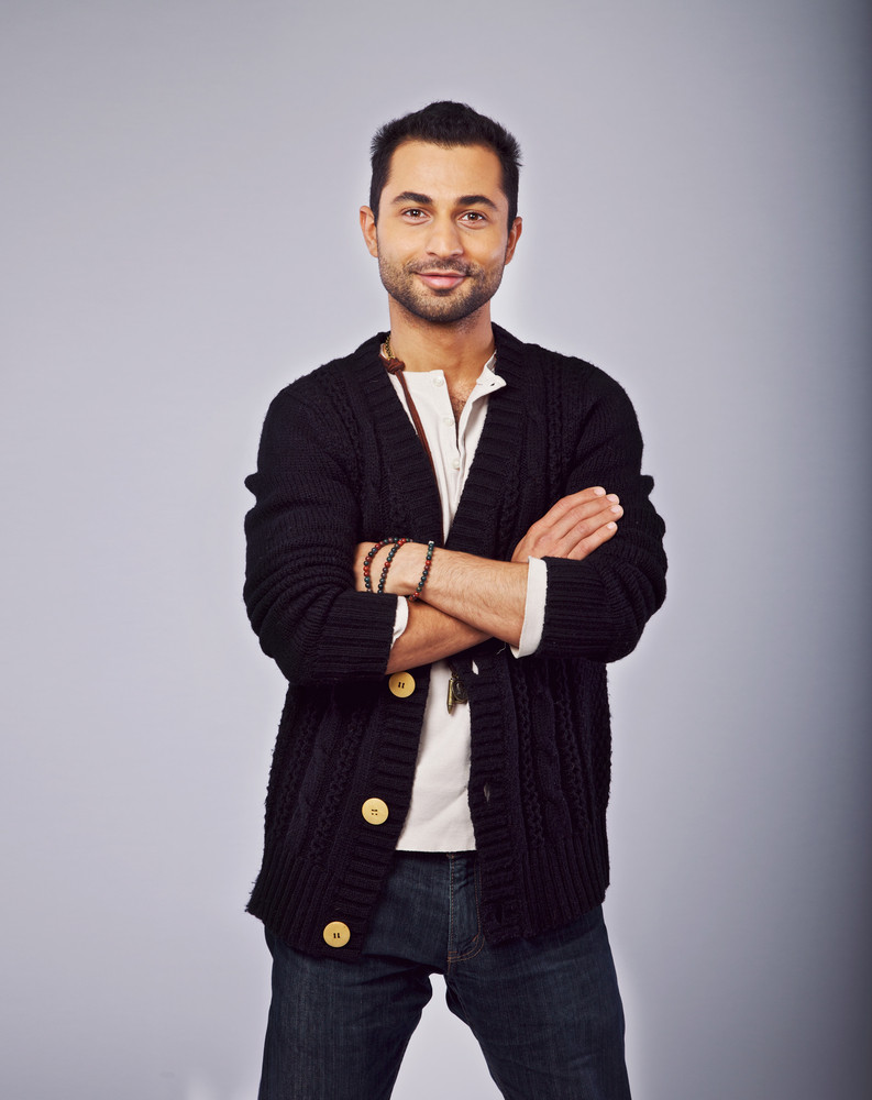 Portrait of a smiling fashionable guy standing in a studio