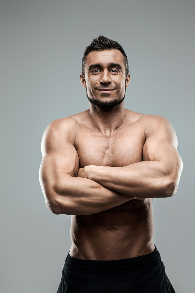 Portrait of a smiling muscular man standing with arms folded