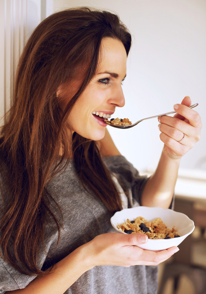 Portrait of a smiling woman at home eating her breakfast