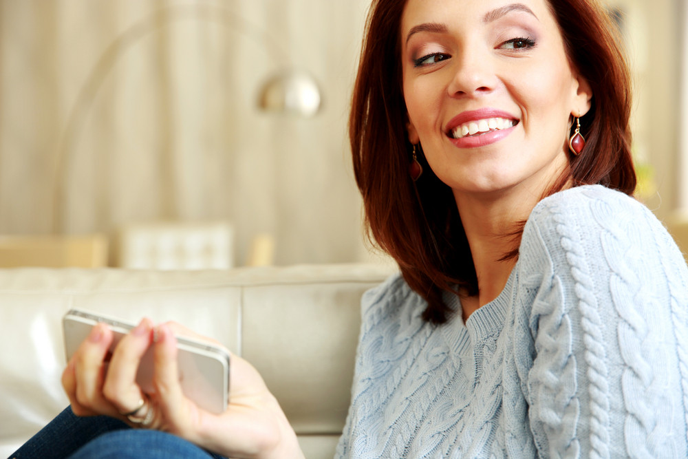 Portrait of a smiling woman holding smartphone at home