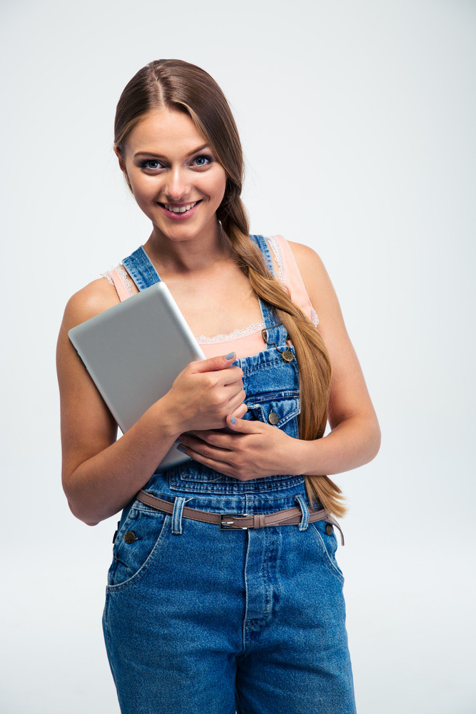 Portrait of a smiling young woman holding tablet computer and looking at camera over gray background