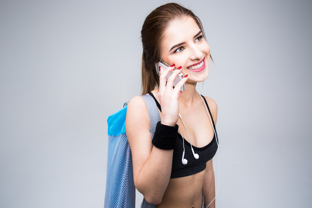 Portrait of a sports woman talking on the phone over gray background