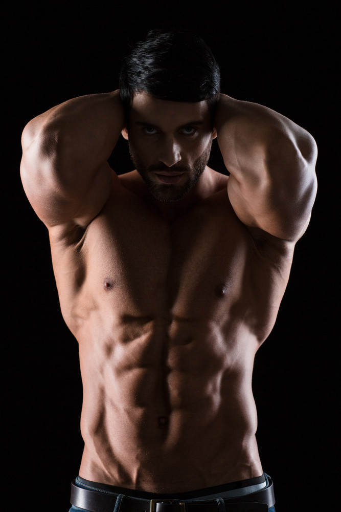 Portrait of a strong muscular man posing on black background