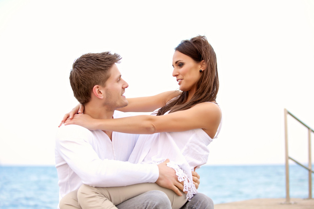 Portrait of a sweet couple  looking at each other enjoying their time on a beach