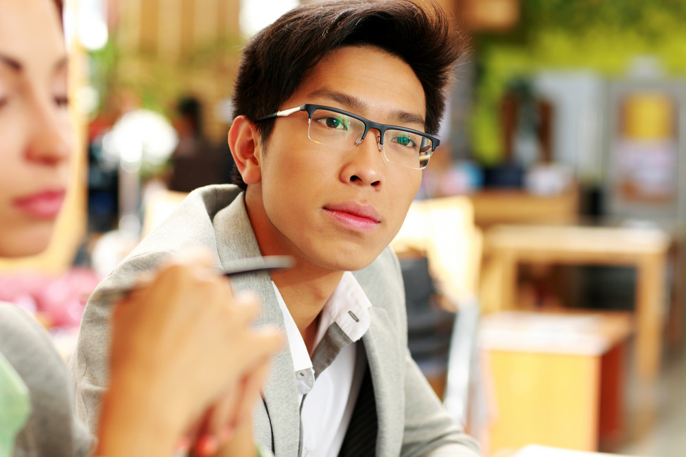 Portrait of a thoughtful asian man in glasses at office