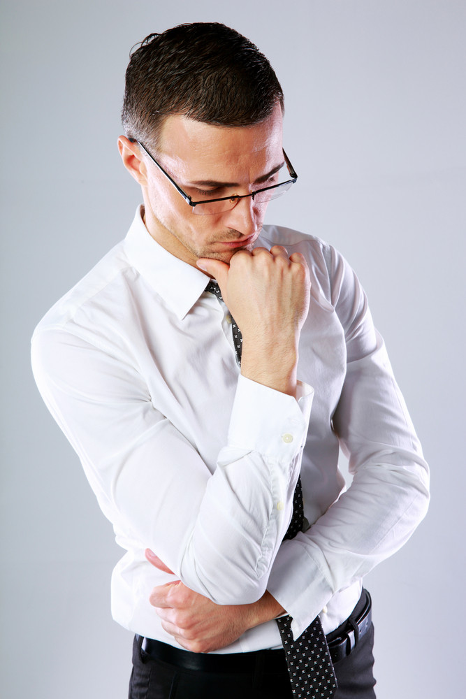 Portrait of a thoughtful businessman in glasses on gray background