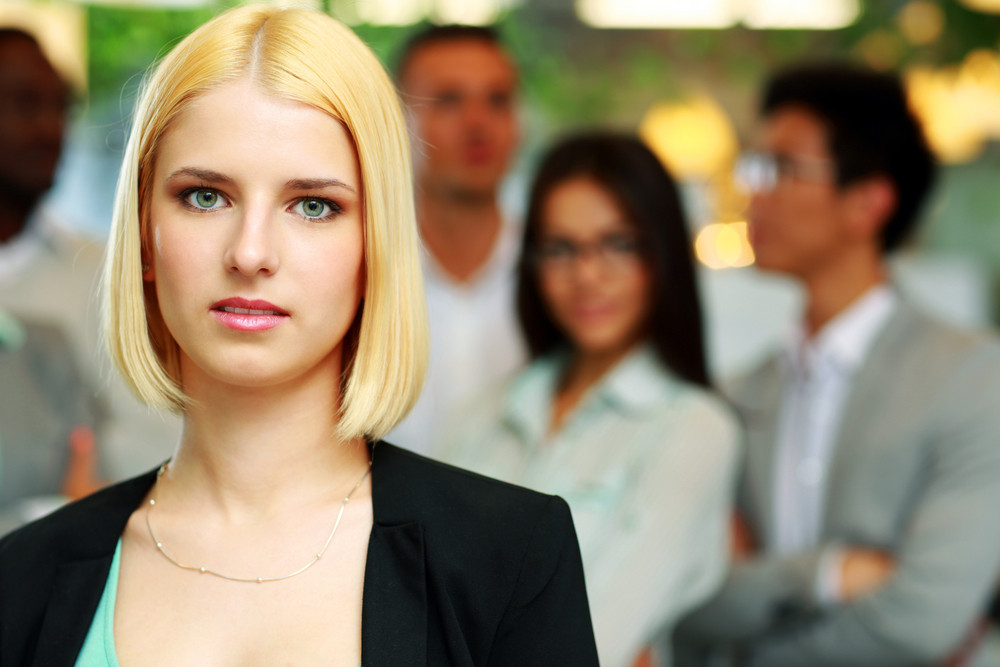 Portrait of a thoughtful businesswoman standing in front of colleagues