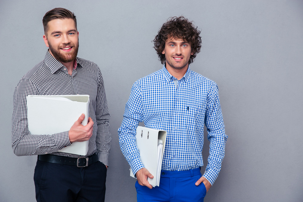 Portrait of a two casual businessmen holding folders