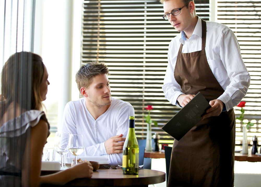 Portrait of a waiter showing the menu to a couple at a restaurant