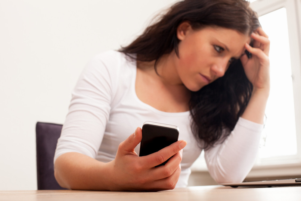 Portrait of a woman with a phone holding her head in frustration