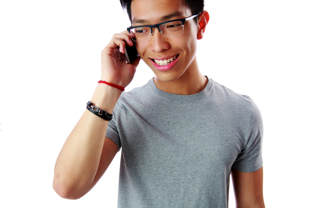 Portrait of a young cheerful asian man talking on the phone over white background