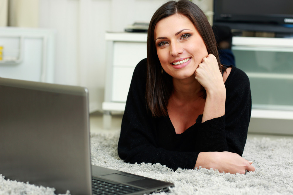 Portrait of a young happy smiling woman lying on the floor with laptop at home