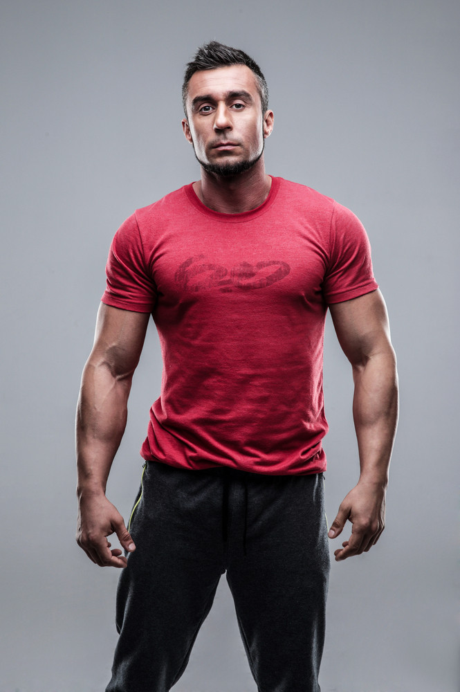 Portrait of a young serious man in red t-shirt over gray background