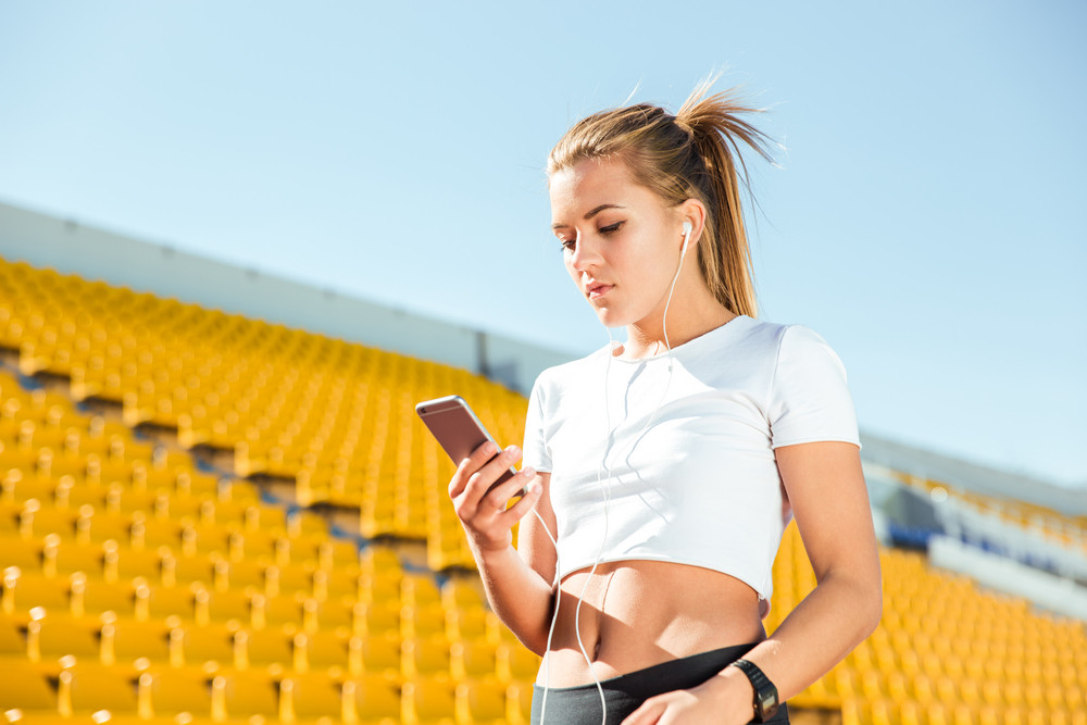 Portrait of a young woman using smartphone with headphones on outdoor stadium