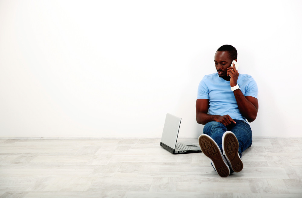 Portrait of african man sitting on the floor and using phone with laptop