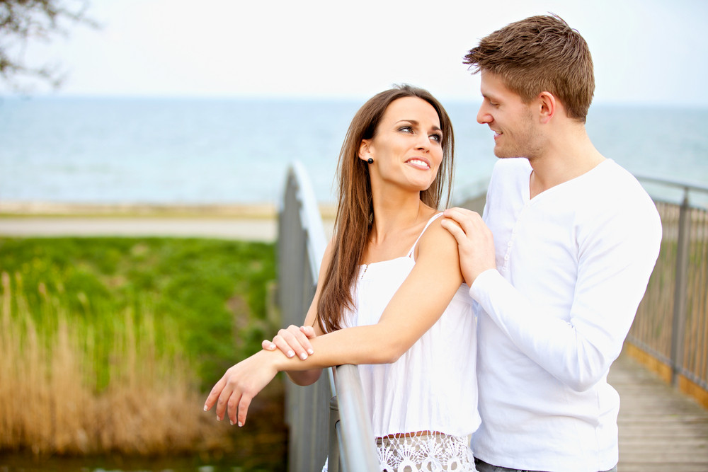 Portrait of an attractive couple looking at each other while dating outdoors