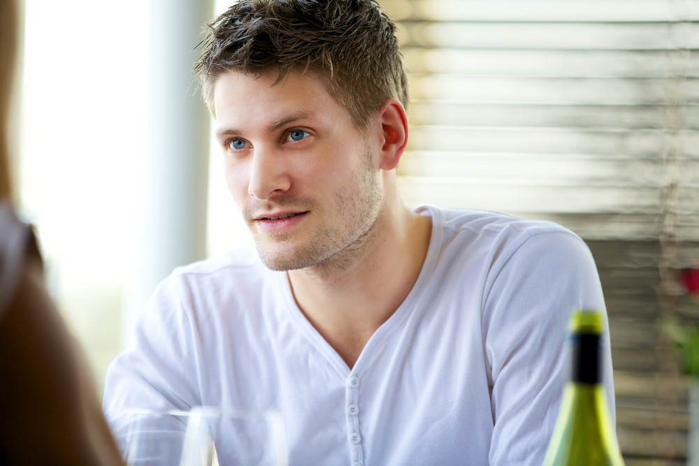 Portrait of an attractive guy seriously listening to someone