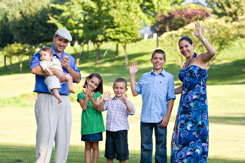 Portrait of an attractive young family with four children waving happily.