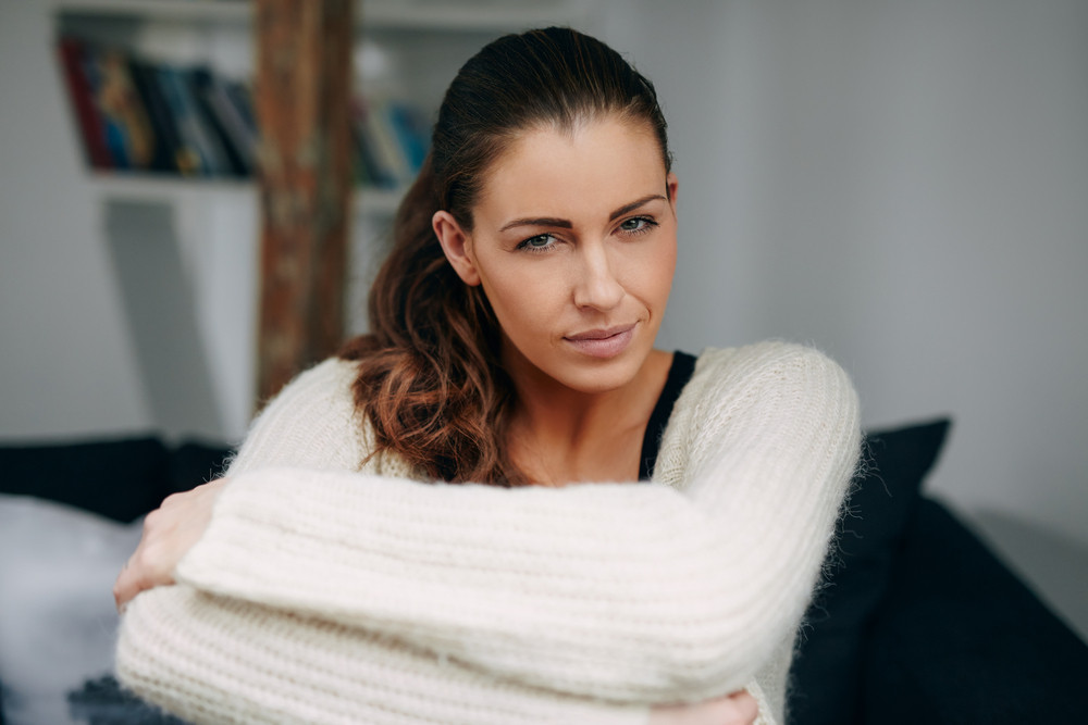 Portrait of attractive young woman sitting at home looking at camera. Pretty relaxed woman indoors.
