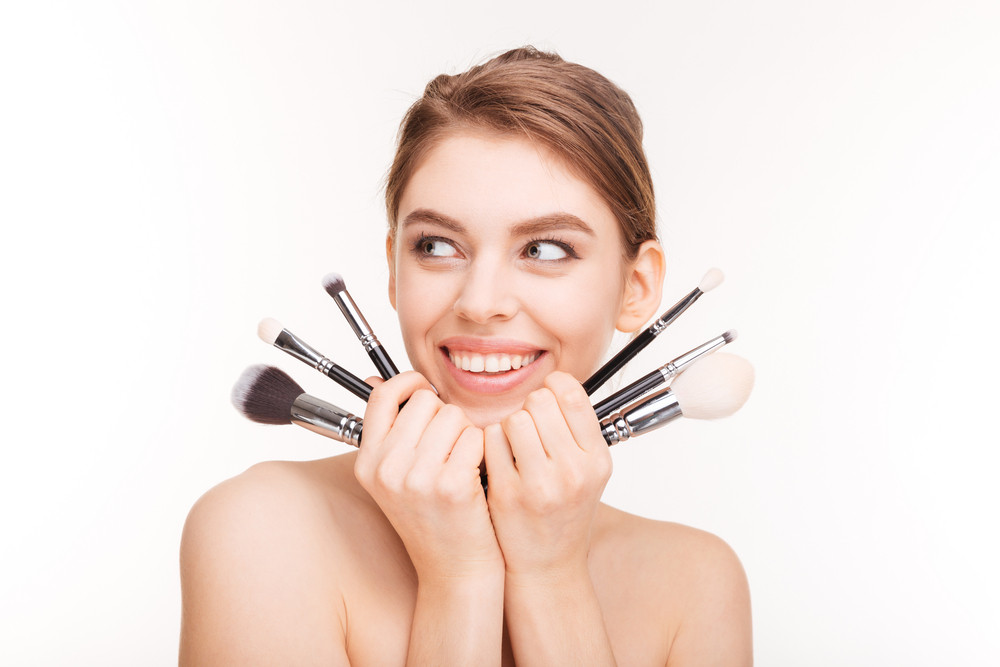 Portrait of beautiful cheerful young woman holding makeup brushes